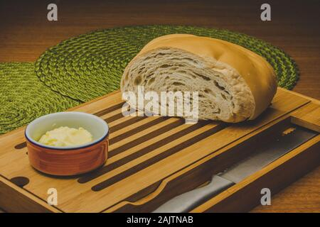 Cutted big bread at the table with knife and butter and placemats - Stock Photo