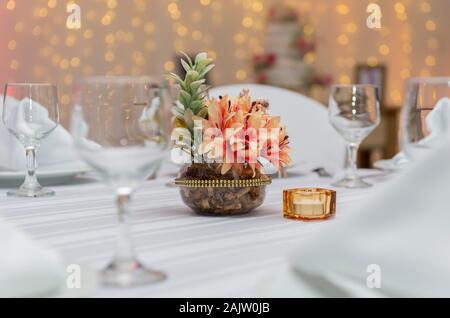 Crystal bowls, fabric napkins and decorative flowers in beautiful vase on a dining table next to a candle. Simple decoration of wedding anniversary. T - Stock Photo