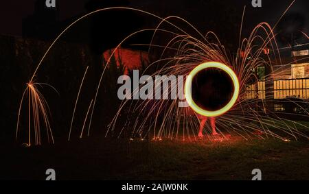 a long exposure photography of an steel wool on fire going in circles and dropping iron on fire as a shower - Stock Photo
