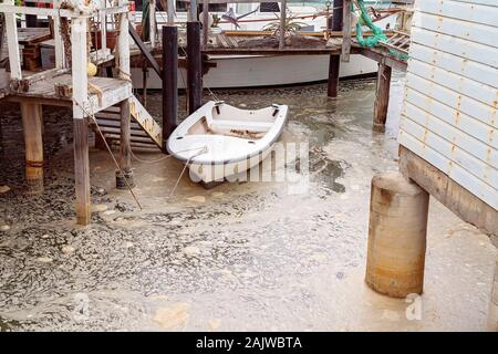 A small white row boat tied up to a post in swirling foamy dirty water at an old timber jetty piled with rubbish - Stock Photo