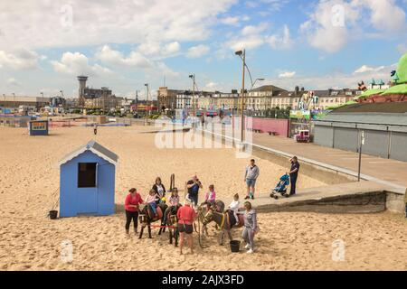 26 June 2019: Great Yarmouth, Norfolk, UK - Children riding donkeys at the beach, with parents assisting. - Stock Photo