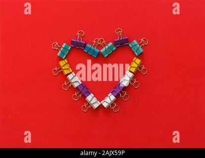 Multicoloured metal office paper clips forming heart shape - Stock Photo