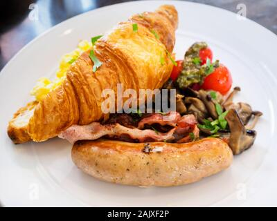 An All-Day breakfast / brunch combo meal platter of scrambled eggs; croissant; sausage; bacon and mushrooms on a white plate at a Western casual resta - Stock Photo