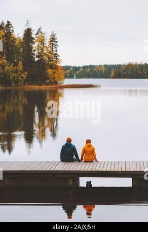 Couple traveling in Finland family lifestyle love relationship man and woman friends sitting on pier outdoor lake and forest landscape autumn season