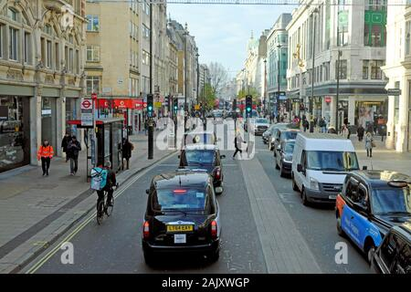 View of taxis, cyclist, traffic queue and people walking on Oxford Street  in West London W1 England Great Britain UK  KATHY DEWITT - Stock Photo