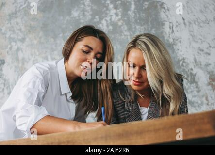 Young successful women colleagues discuss joint project, coaching or mentoring at the table - Stock Photo