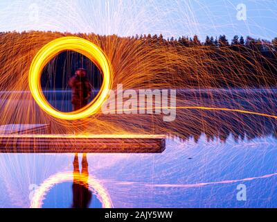 burning steel wool spinning, showers of glowing sparks from spinning steel wool, beautiful reflections in water - Stock Photo