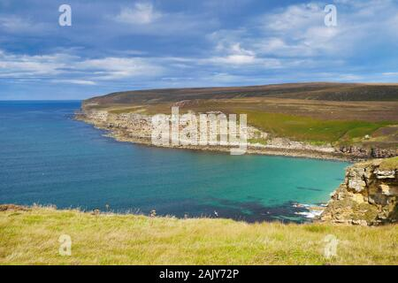Coastline in Caithness, Scotland, UK on a calm, sunny day at the end of summer, showing the rock strata in the coastal cliffs against turquoise water - Stock Photo