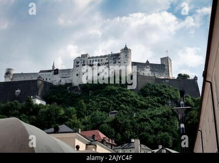 View of Hohensalzburg fortress from below with modern funicular trains going up and down. Hill covered in green bushes, trees and railroads. Old town. - Stock Photo