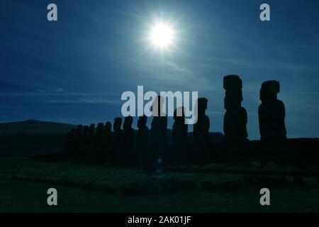 Pop art style blue colored gigantic Moai statues silhouette at Ahu Tongariki against sky with dazzling sun, Easter Island, Chile - Stock Photo