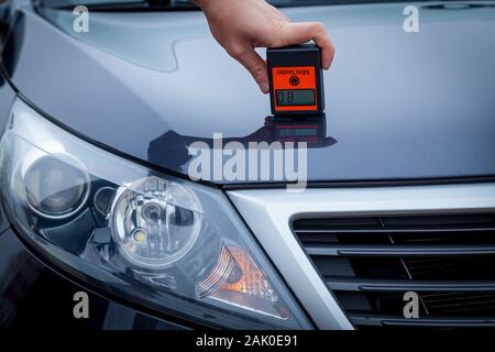 Measuring the thickness of the car paint coating in black color using a paint thickness gauge. - Stock Photo