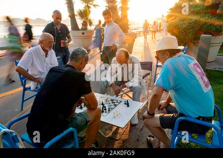Male friends and spectators enjoy a game of chess, Boulevard de la Croisette, Cannes, Provence, France, Europe
