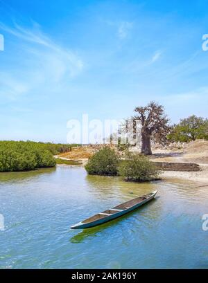 Traditional colorful wooden boat on the river in sea lagoon and a beautiful sky in the background, Africa, Senegal.