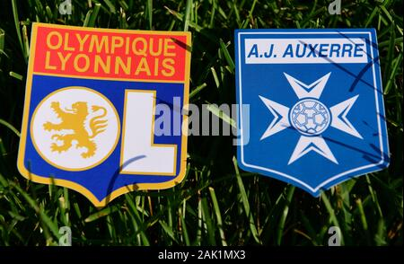 September 6, 2019, Paris, France. Emblems of french football clubs Olympique Lyonnais and Auxerre on the green grass of the lawn. - Stock Photo