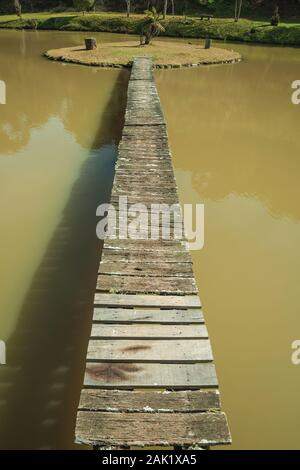 Wooden walkway going to a small island in pond from a garden with palm trees near Bento Goncalves. A wine producing country city in southern Brazil.