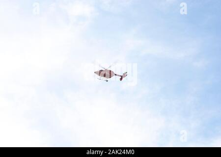 Red rescue helicopter making landing approach in the distance - Stock Photo