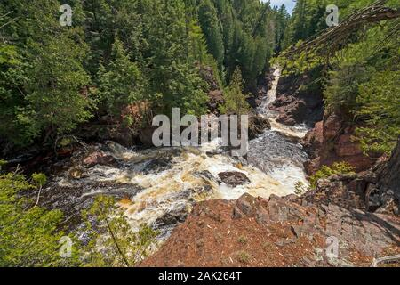 Water Rushing Down a Narrow Gorge in Copper Falls State Park in Wisconsin - Stock Photo