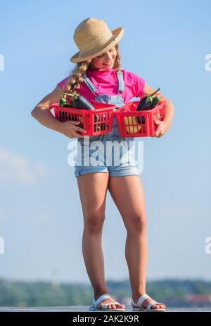 Girl cute child farming. Gathering vegetables in basket. Village rustic style. Vegetables market. Sunny day at farm. Selling homegrown food concept. Natural vitamin nutrition. Organic vegetables. - Stock Photo