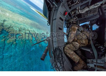 PICTURE SHOWS: U.S. Air Force Tech. Sgt. Keon Miller, special mission aviator assigned to the 33rd Rescue Squadron, looks out the gunner's window aboard an HH-60G Pave Hawk, July 31, 2019, out of Kadena Air Base, Japan. The HH-60G Pave Hawk is capable of performing peacetime operations such as civil search and rescue, emergency aeromedical evacuation, disaster relief, international aid and counter-drug activities. (U.S. Air Force photo by Airman 1st Class Matthew Seefeldt)   ....   STORY COPY:  Meet the real Top Guns.   These jaw-dropping photographs have been hand-picked by Airman Magazine, t - Stock Photo