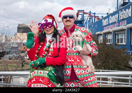 Posed portrait of a couple & their dog in ugly Christmas outfits on the Boardwalk in Coney Island on the day of the Polar Bear New Years day swim. - Stock Photo
