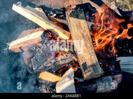 Bonfire with orange flames, new logs and a beautiful hot glow burning outdoors in a firebowl made of steel. Seen in Bavaria, Germany in January - Stock Photo