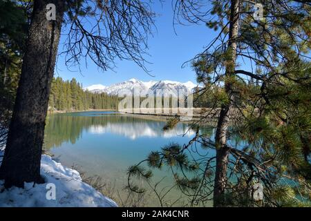 View of Two Jack Lake in Banff National Park, Canada with the snow-capped Canadian Rockies and the reflection of the scenery in the turquoise water - Stock Photo