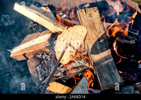Toasting a piece of bread on a wooden stick above a bonfire with orange flames and a beautiful hot glow in a firebowl. Seen in Bavaria, Germany in Jan - Stock Photo