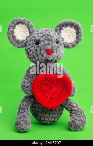 Grey knitted mouse with a heart in hand on a green background - Stock Photo