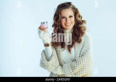 smiling stylish woman with long wavy hair in neck sweater and cardigan with winter skin care facial creme isolated on winter light blue background. - Stock Photo
