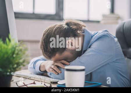 Fell asleep. Young bearded man in blue shirt having a nap at working place - Stock Photo