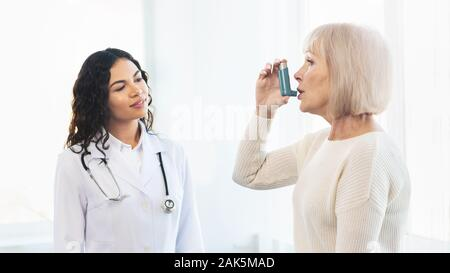 Medical Advice. Elderly woman using asthma inhaler, mexican doctor watching, free space, panorama - Stock Photo