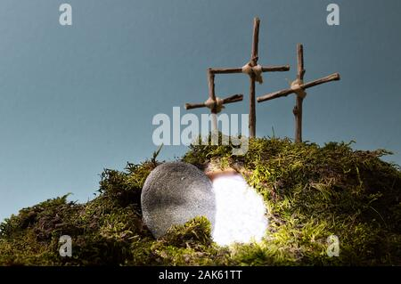 resurrection garden as easter decoration with a stone near the empty tomb filled with blinding light and three crosses on a hill above - Stock Photo