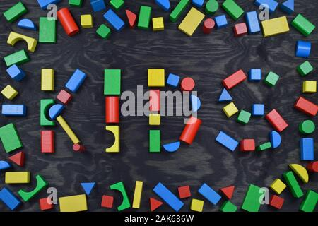 the word KIDS out of colorful wooden toy blocks on black wooden background with frame out of toy blocks - Stock Photo