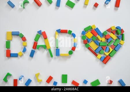 colorful wooden toy blocks lettering the word DAD and a heart on white background - Stock Photo