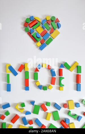 colorful wooden toy blocks lettering the word MOM and a heart on white background - Stock Photo