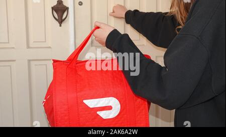 Person knocking on a door, making a DoorDash delivery. - Stock Photo