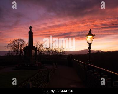 War Memorial in the Castle Grounds silhouetted against a sunset sky at Knaresborough North Yorkshire England