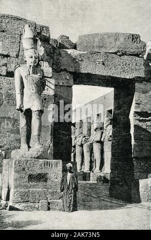 This illustration of the ruins of the Statue of Ramses II Iand his Temple at Karnak dates to the early 1900s. The nearly 200-foot-long temple features three chapels, a hypostyle hall with eight columns, a vestibule with four columns, and an open court. The court is surrounded by statues of Ramses III in his Jubilee vestments (can see in left background). A statue of Ramses stands by the entranceway here. Ramses III (died c.1155 B.C.) was the second Pharaoh of the Twentieth Dynasty in Ancient Egypt. - Stock Photo