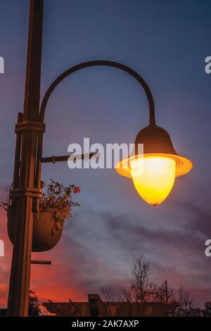 Detail of a decorative light post and colorful sky at sunset in Gramado. A cute european-influenced town in southern Brazil. - Stock Photo