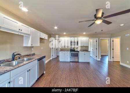 Horizontal shot of the kitchen interior of a new small tract home. - Stock Photo