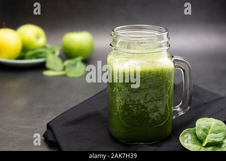 Healthy green smoothie in a mason jar mug dark food photo. Healthy food concept. - Stock Photo