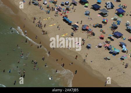 Durban, KwaZulu-Natal, South Africa, aerial view, landscape, umbrellas of people sun bathing and swimming, local tourists, Amanzimtoti, Doonside beach - Stock Photo