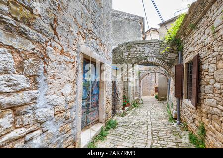 Typical narrow cobbled alleyway with stone arches in the historic old town in Bale, a small hill town on Mont Perin in Istria County, Croatia