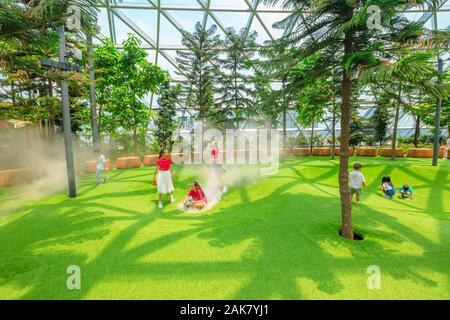 Singapore - Aug 8, 2019: funny children at Foggy Bowls, a simple playground features bowl-shaped platforms with artificial lawn which release mists - Stock Photo