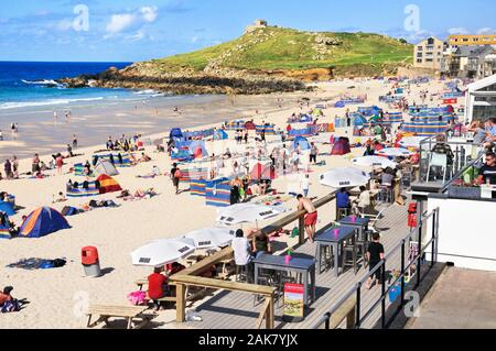 Holidaymakers enjoying the sun on Porthmeor beach in high summer at the popular seaside resort of St Ives in Cornwall, England, UK - Stock Photo