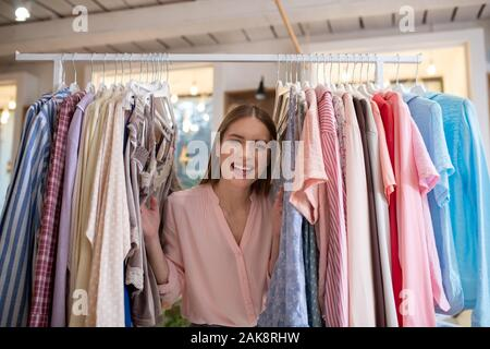 Happy and smiling young woman standing among clothes - Stock Photo