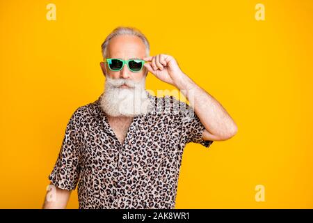 Photo of serious confident old man holding his glasses staring into camera while isolated with yellow background - Stock Photo