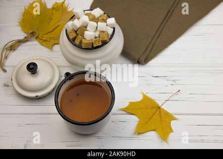tea in an aluminum cup and sugar cubes in an aluminum sugar bowl, brown scarf, maple leaves on a light wooden background - Stock Photo
