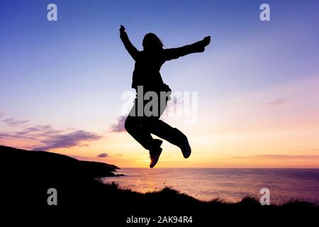 Silhouette of woman jumping for joy on coastal clifftops at sunset - Stock Photo