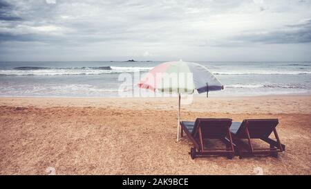 Two sunbeds and umbrella on an empty beach, color toning applied, Sri Lanka. - Stock Photo